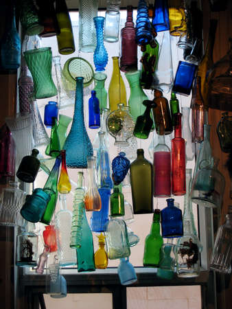 Colorful glass bottles hanging in a window
