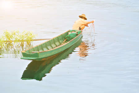green boat: Asian fisherman on green boat colecting net trap in the river.