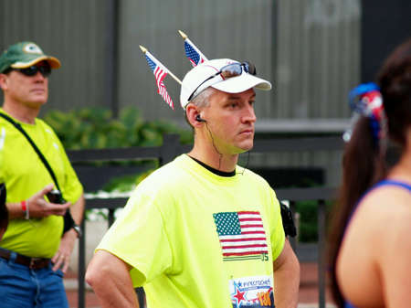 Man wearing US flags in hat waits for start of charity race.