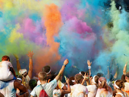 jubilation: Color covered charity run finishers celebrate by throwing colored powder into air.
