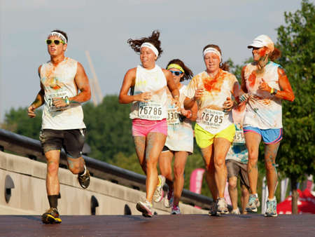 colorful: A mixed gender group of runners covered in colored powder participating in charity run. Stock Photo