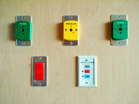 Medical oxygen, air, and emergency call buttons on hospital wall.