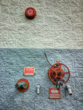 suppression: Circular red fire suppression equipment against blue and gray square block wall.
