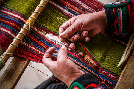 Webende Frau, handgemachte bunte Materialien. Chinchero, Peru.