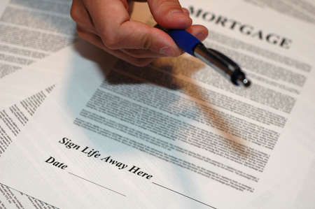 hand holding pen: Mortgage Documents with Hand Holding Pen