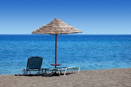 sun bathing: An umbrella and sun bathing chairs on the black beach of Perissa, in the Greek Islands.
