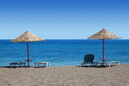 sun bathing: Umbrellas and sun bathing chairs on the black beach of Perissa, in the Greek Islands.