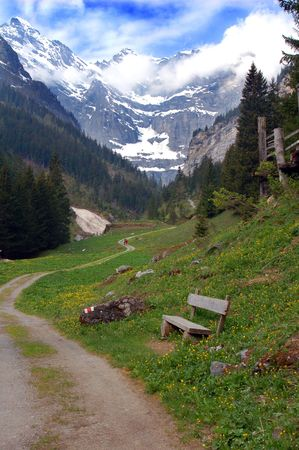 A trail leads through a beautiful valley, with a bench to stop and enjoy the view. Stock Photo - 945358
