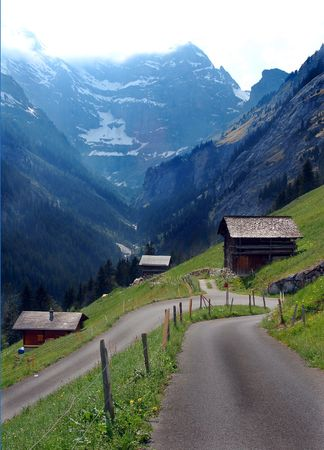 A road winds through a small alpine villiage in Switzerland. Stock Photo - 945360