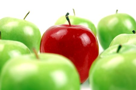 extraordinary: A red apple stands out as unique among a bunch of green apples.  Shallow DOF. Stock Photo
