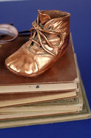 bronzed: Bronzed  shoe and old books and glasses.