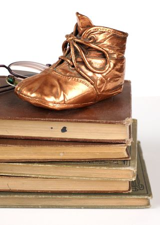 bronzed: Bronzed baby shoe and books from a persons life.