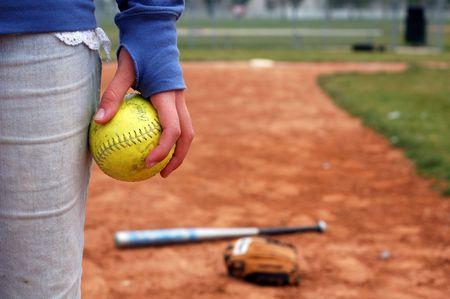 A girl holds a softball on the infield diamond. Stock fotó