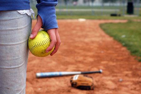 infield: A girl holds a softball on the infield diamond. Stock Photo