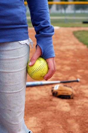 mitt: A young woman holds a softball.  Mitt and bat are out of focus on the infield.