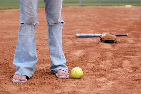 A Girl stands in the infield wearing flip flops. photo