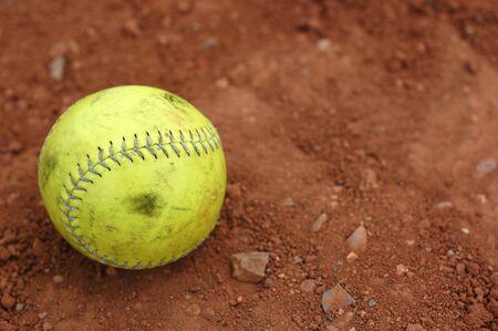 softbol: Un bien utilizado amarillo softbol en el infield suciedad.  Foto de archivo