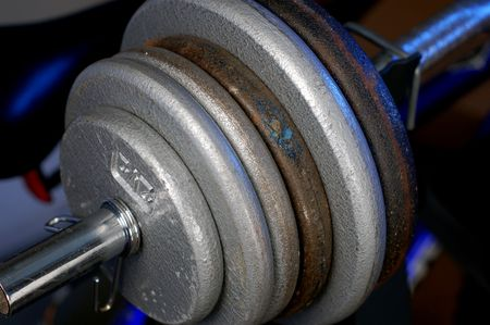 A bunch of weights on a weight lifting bar, resting on a weight bench.