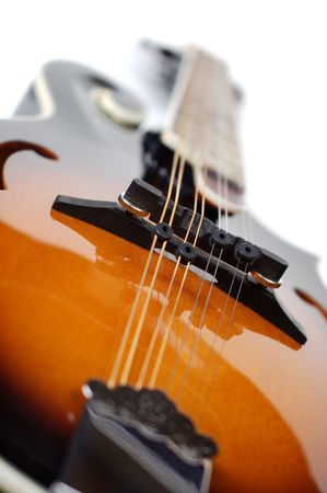 tune: Close up of a mandolin on a white background.