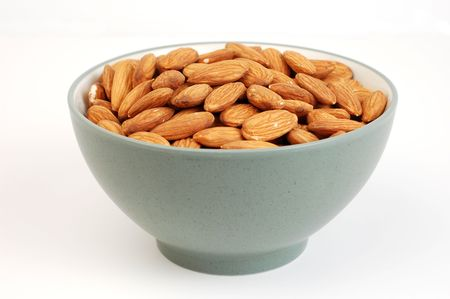 shelled: A bowl of shelled almond nuts on a white background. Stock Photo