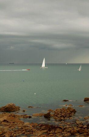 Sailboats against a beautiful dark cloudy sky in the Irish Sea. Stock fotó