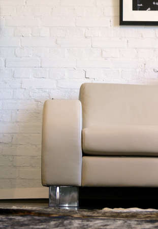 A leather sofa by a white brick wall Imagens