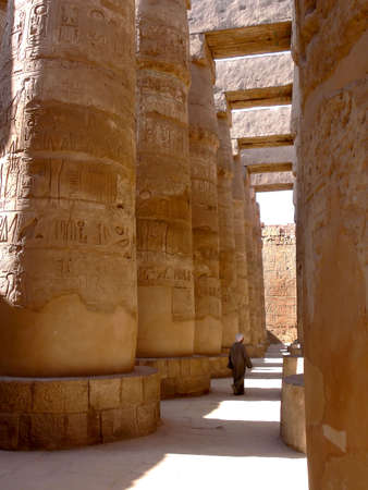 An egyptian walking through the pillar hall of the Karnak temple in Luxor Egypt