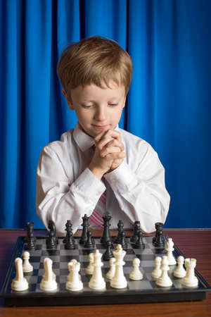 handcarves: boy in white shirt playing chess on a blue background