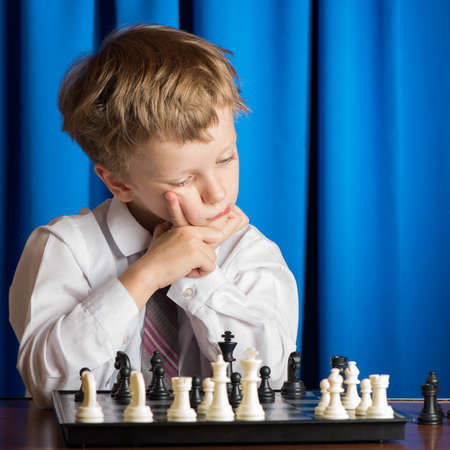 playing  chess: boy in white shirt playing chess on a blue background