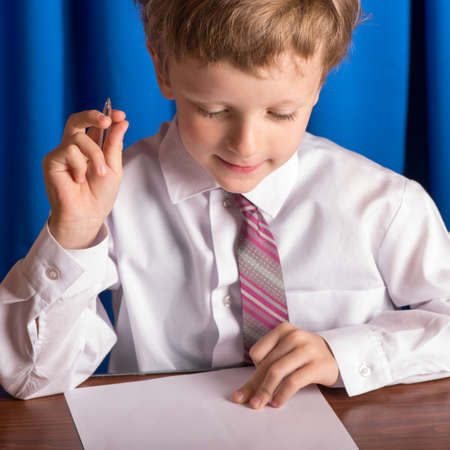 handcarves: The boy writes with a ballpoint pen on a white sheet of paper