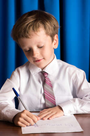 studious: The boy writes with a ballpoint pen on a white sheet of paper