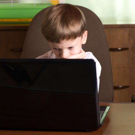 rested: boy with laptop at the table looking at the monitor and rested her chin in the palm of Stock Photo