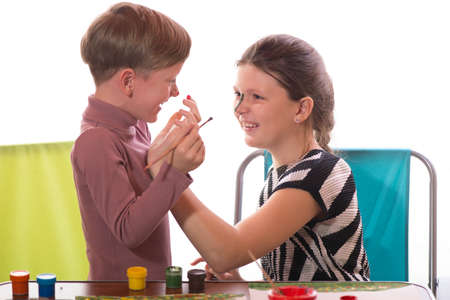 caritas pintadas: a boy and a girl having fun painting face painting Foto de archivo