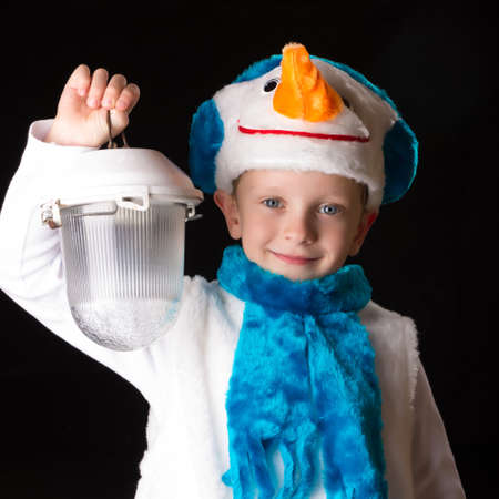 desired: boy in a Christmas costume held down a flashlight Stock Photo