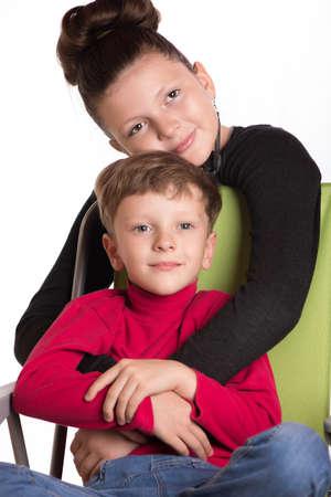 nene y nena: El ni�o y la ni�a se abrazaron y se mantienen para las manos.