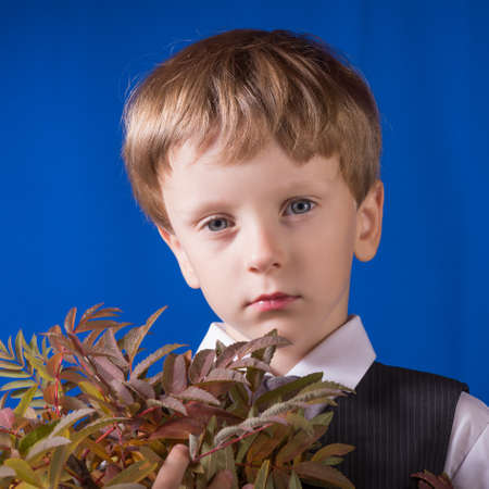 despondency: Portrait of the boy of the blonde with blue eyes with a bouquet in hands Stock Photo