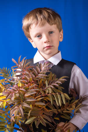fullface: Portrait of the boy of the blonde with blue eyes with a bouquet in hands Stock Photo