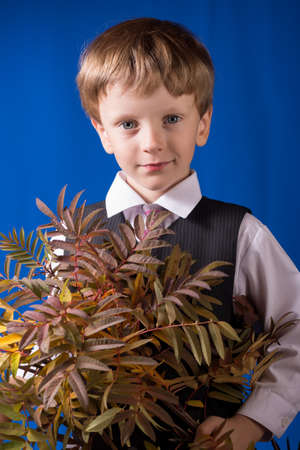 blond boy: Portrait of the smil boy of the blonde with blue eyes with a bouquet in hands Stock Photo
