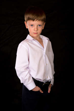 blond boy: Portrait of a boy on a black background with the white shirt. Blue eyes blond. Different camera angles while standing.