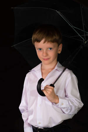 boy smiling: Portrait of a boy on a black background with the white shirt. Blue eyes blond. With umbrella in hand while standing.