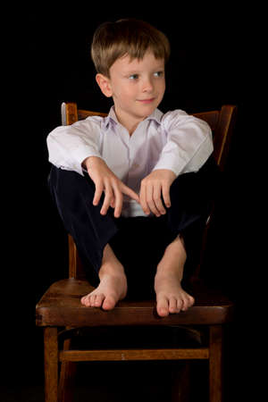 full face: Portrait of a boy on a black background with the white shirt. Blue eyes blond. Sitting on a vintage stool with her bare feet.