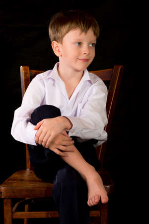 boy barefoot: Portrait of a boy on a black background with the white shirt. Blue eyes blond. Sitting on a vintage stool with her bare feet.