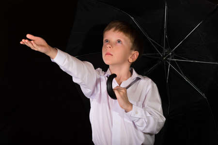 Portrait of a boy on a black background with the white shirt. Blue eyes blond. With umbrella in hand while standing.