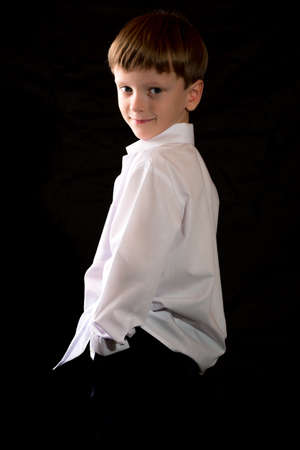 full face: Portrait of a boy on a black background with the white shirt. Blue eyes blond. Different camera angles while standing.