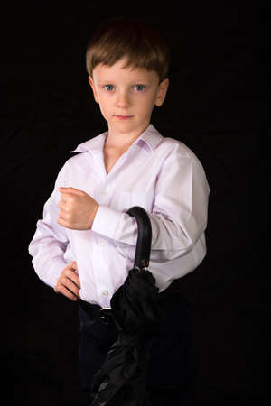 full face: Portrait of a boy on a black background with the white shirt. Blue eyes blond. With umbrella in hand while standing.