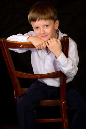 full face: Portrait of a boy on a black background with the white shirt. Blue eyes blond. Sitting on vintage chair.
