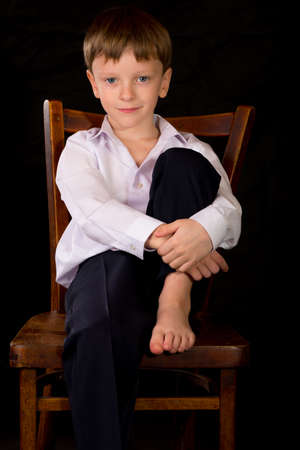 boy smiling: Portrait of a boy on a black background with the white shirt. Blue eyes blond. Sitting on a vintage stool with her bare feet.