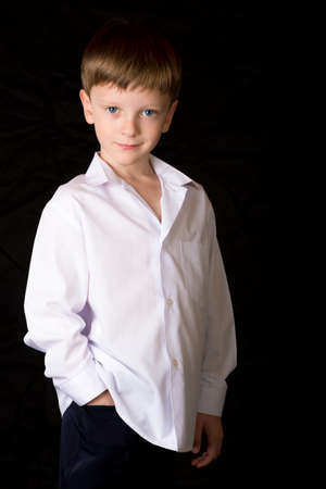 boy barefoot: Portrait of a boy on a black background with the white shirt. Blue eyes blond. Different camera angles while standing.