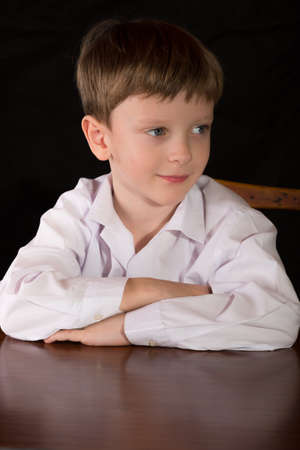 blonde boy: Portrait of a boy on a black background with the white shirt. Blue eyes blond. Sitting at the table.