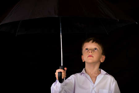 blond boy: Portrait of a boy on a black background with the white shirt. Blue eyes blond. With umbrella in hand while standing.